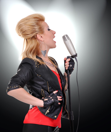 rock girl singer with microphone on black background photo
