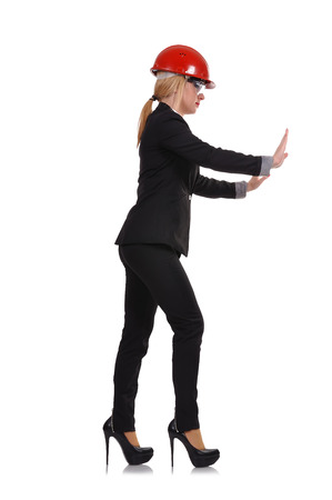 invisible object: woman engineer with helmet pushing an invisible object