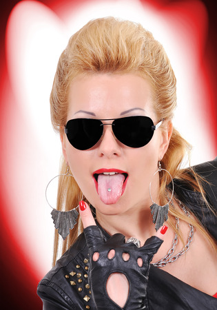 rocker girl: Muchacha atractiva del eje que muestra la lengua Foto de archivo