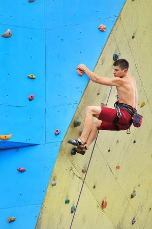 fitness hombres: Escalada escalador joven en una pared