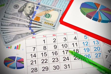 Workplace with calendar and dollars on a wooden work table Stock Photo