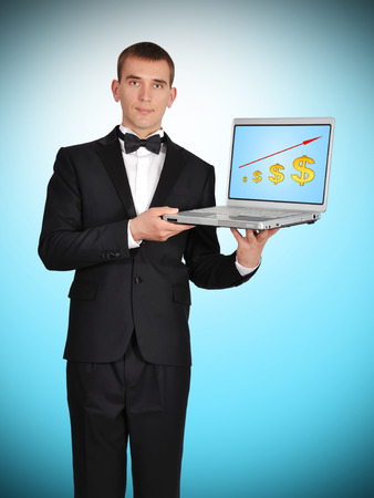 businessman in tuxedo holding laptop with chart on screen photo