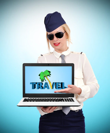 commercial tree service: stewardess holding laptop with  travel symbol on blue background Stock Photo