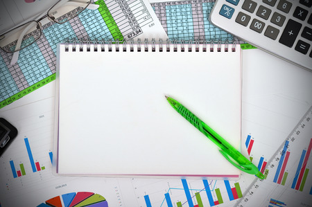 blank notebook and financial charts photo
