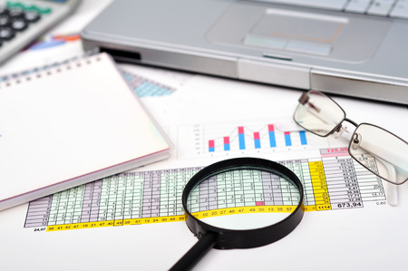 market analysis concept with financial report, pen, laptop and magnifying glass photo