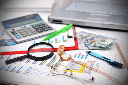 Close-up of business document, pocket watch, money and calculator  on desk photo