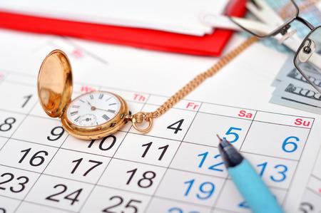 antique gold pocket watch, calendar and pen photo
