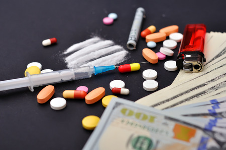 narcotic: lines of heroin beside a wrapped up dollar bill and narcotic tablets Stock Photo