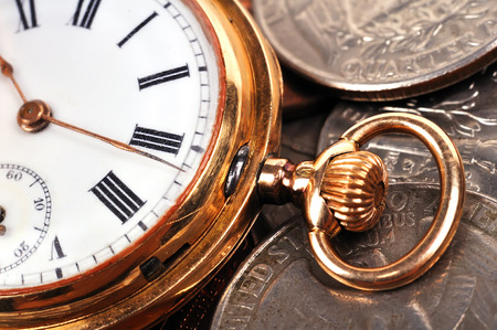 Pocket gold watch and coins, close up photo