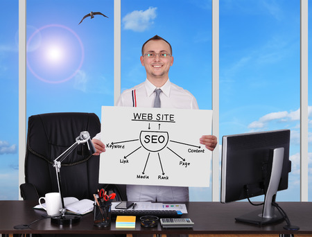 businessman in office holding placard with plan seo photo