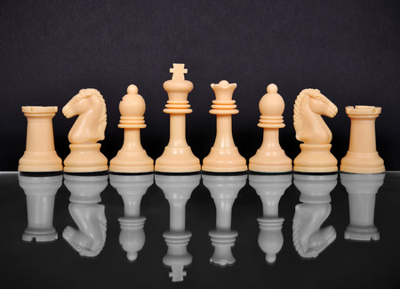 White chess pieces with reflection on black background photo