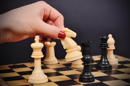 chess rook: hand holding white chess knight on chessboard