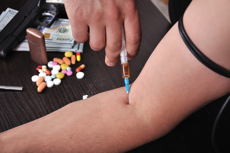 hijacker: Drug addict man with syringe in action Stock Photo