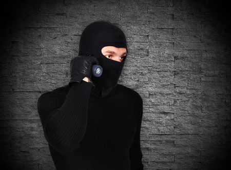 mugger: mugger with flashlight on a gray background Stock Photo