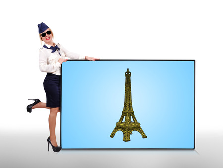 happy stewardess holding plasma panel with eiffel tower photo