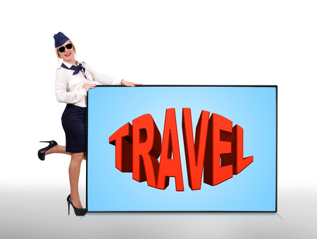happy stewardess holding plasma panel with travel symbol photo