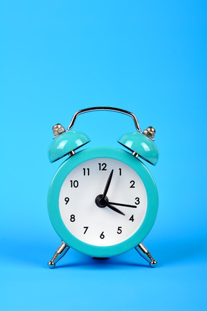 old style alarm clock isolated on blue