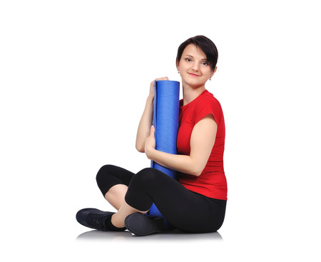 karemat: sporty girl sitting with mat for fitness