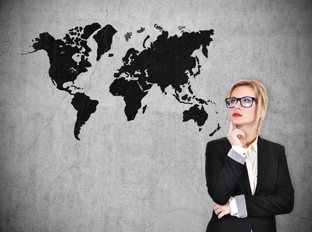 world thinking: businesswoman thinking and looking on world map