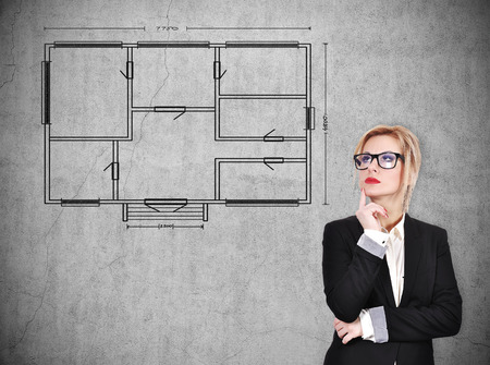 cement solution: businesswoman thinking and looking on blueprint on concrete wall