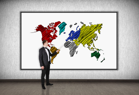 businessman with a pointer points to desk with world map photo