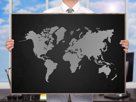 businessman holding blackboard with drawing world map photo