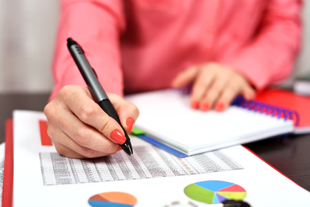 financial: woman with pen checks the financial report