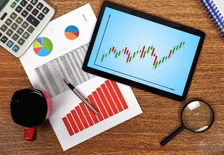 stock predictions: tablet with stock graph on wooden table