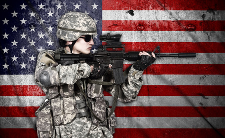 fatigues: soldier holding rifle on american flag background Stock Photo