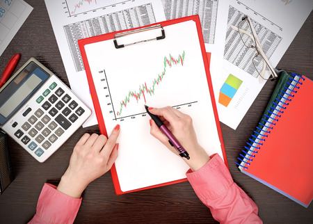 stock predictions: woman drawing stock chart on clipboard sitting in office