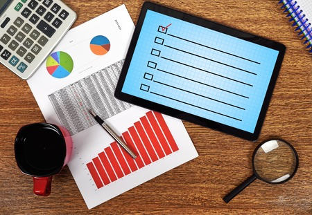 stock predictions: digital tablet with checklist on the table businessman Stock Photo