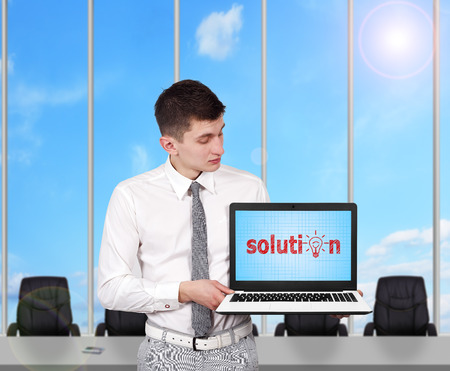 young businessman holding laptop with solution symbol photo