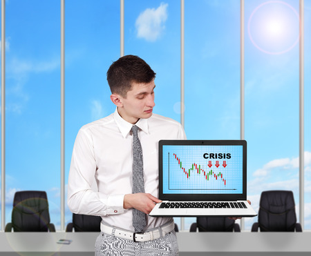 businessman holding laptop with crisis concept photo