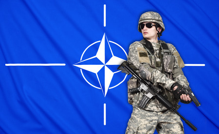 fatigues: US soldier with gun on a Nato flag background Editorial
