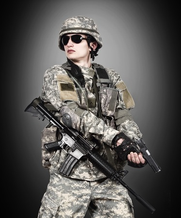 fatigues: US soldier holding gun on a black background