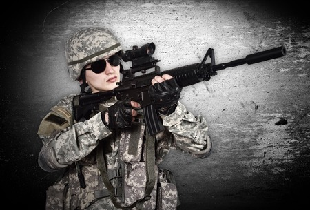 fatigues: US soldier with rifle on a gray background Stock Photo