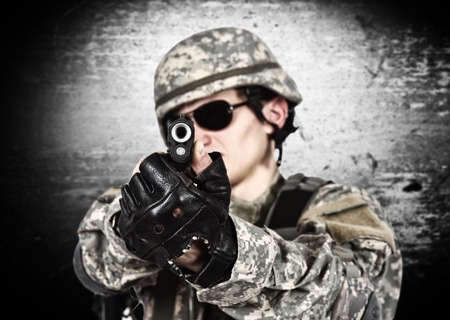 fatigues: USA soldier aiming a gun  on gray background