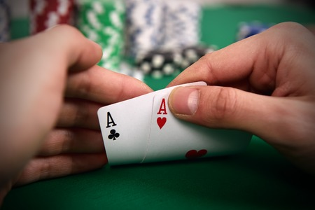 casino table: poker player with two Aces and chips at green casino table