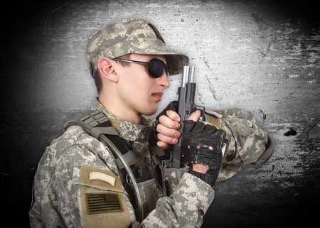 militant: soldier with gun on a gray background Stock Photo