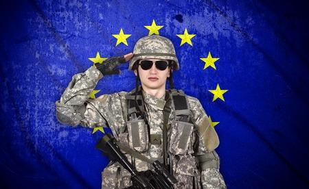 european union flag: soldier salutes the European Union flag on the background