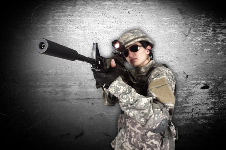 fatigues: soldier holding his assault rifle isolation on gray
