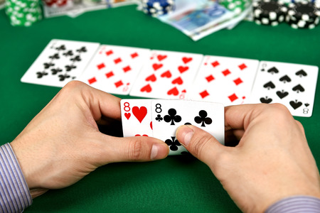 eights: poker player with two eights and chips at green casino table Stock Photo