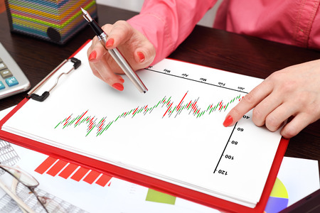 stock predictions: woman drawing on clipboard with stock chart Stock Photo