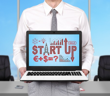 young businessman holding laptop with start up concept photo