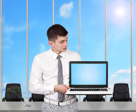 young businessman holding laptop with blank screen photo