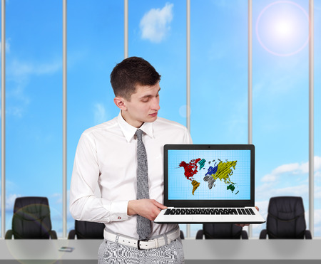 young businessman holding laptop with world map photo