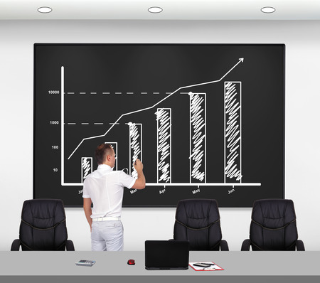 stock predictions: businessman drawing stock chart on chalk board Stock Photo