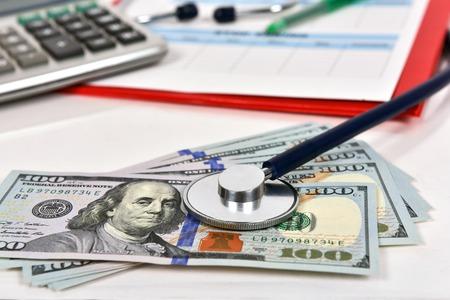 medical bills: medical stethoscope on dollar bills, extra close up