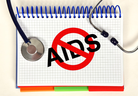 open book with stop aids symbol and stethoscope on tab photo