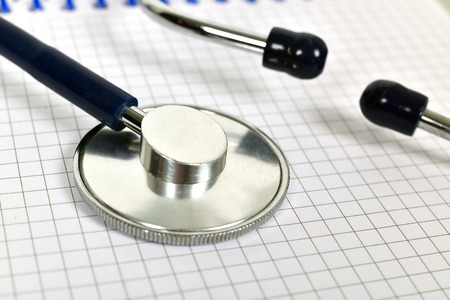 note pad: Stethoscope on blank note pad, close up